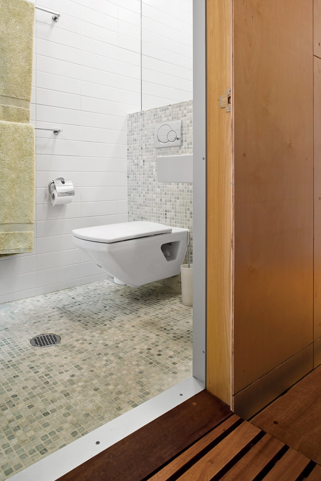 A skylight in the compact bathroom opens the space, and green tiles give the room a spa-like feel.  Photo 13 of 13 in Tips for Tiny Bathrooms from Storage-Smart Renovation in New York City