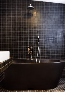 Black tiles and fittings lend the bathroom a dramatic look. The black bathtub is made of recycled plastic. Photo by Per Magnus Persson.