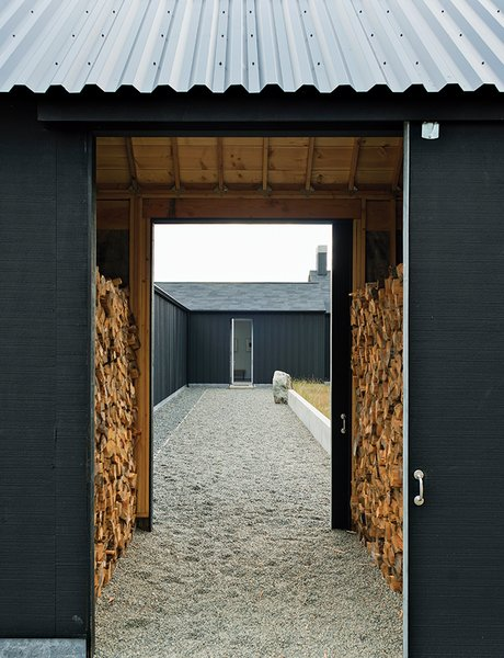 The gravel path leading to the front door passes through firewood storage and the central courtyard.