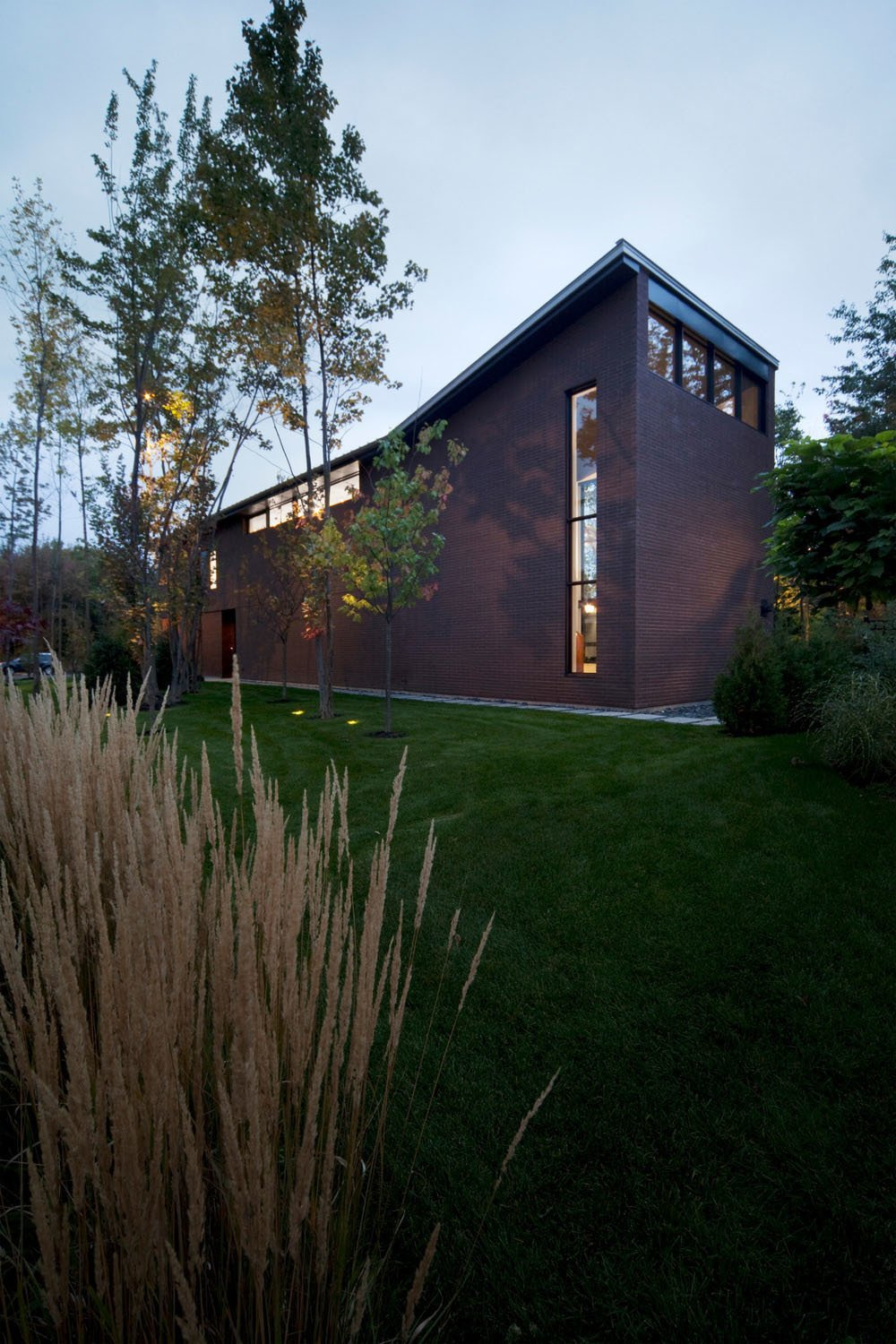 Openings were limited on the side of the cedar-and-brick building that faces the street, allowing for expansive views of the veranda and yard from the rear.  Photo 2 of 7 in Near Montreal, a House Connects With Its Surroundings
