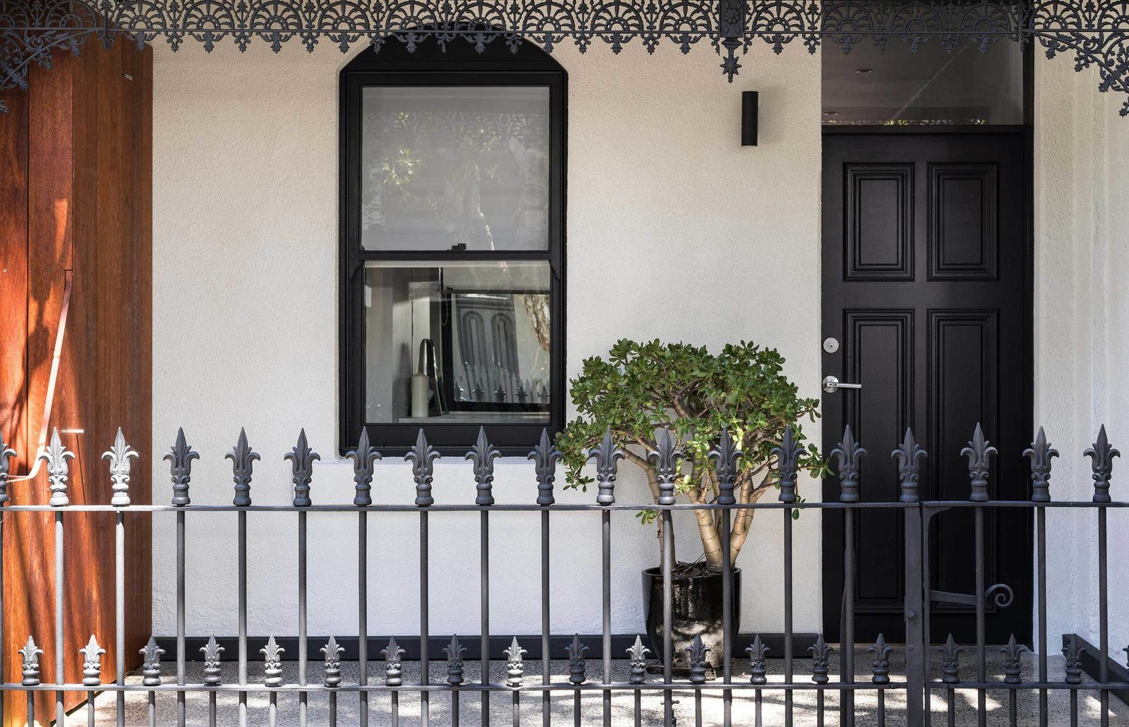 The home's white stucco walls and chestnut-hued timber offer a modern contrast to its filigree railing and ornamentation.  Photo 1 of 7 in Renovated 19th-Century Terrace House Merges with the Outdoors