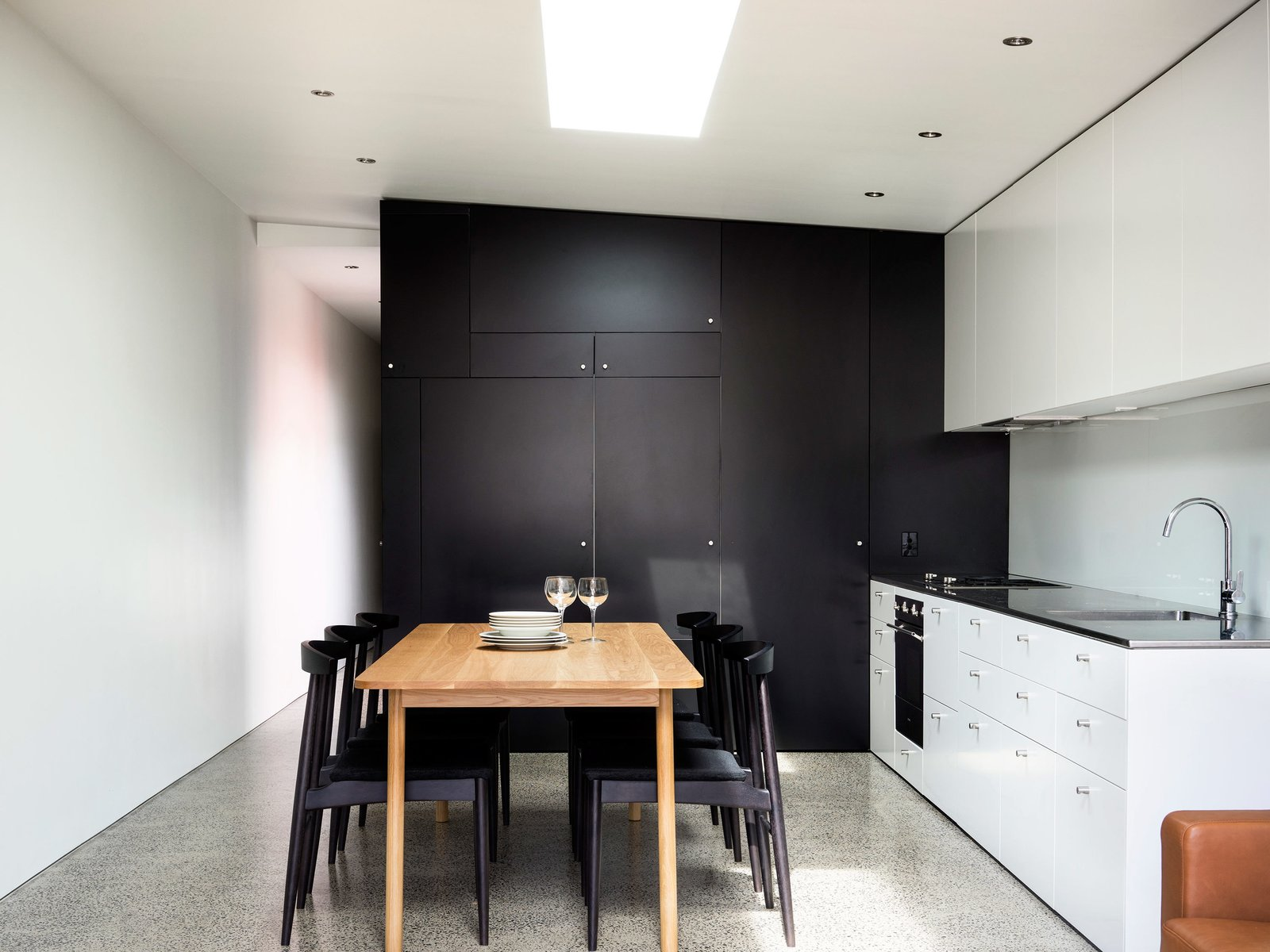 The home's minimalist kitchen demonstrates that you can create something beautiful without shelling out too much cash. To help stretch the budget, Abicic installed generic fixtures and cabinets. The dining room chairs and table were purchased secondhand.  Photo 4 of 7 in Renovated 19th-Century Terrace House Merges with the Outdoors