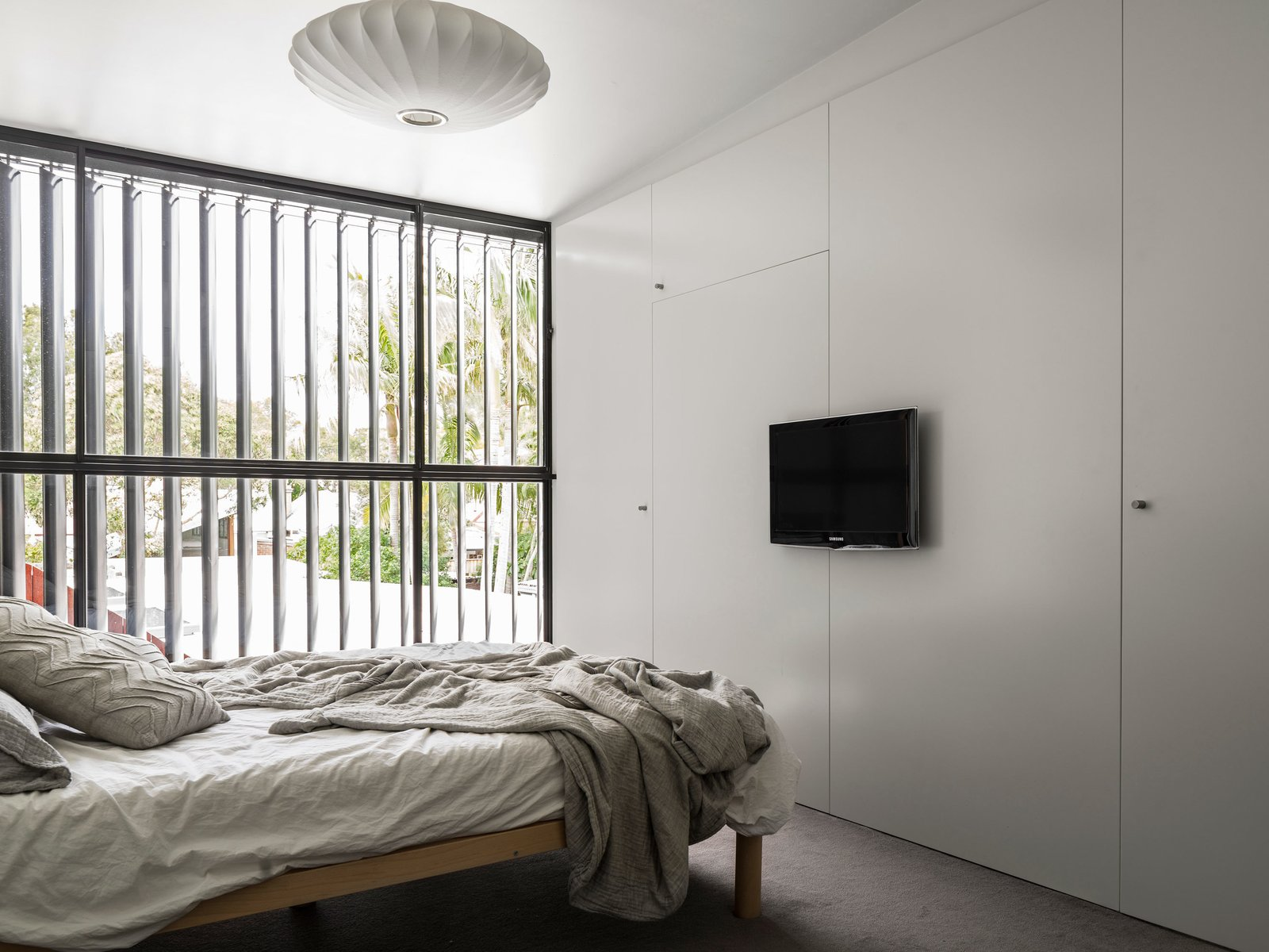 Bedroom, Bed, Pendant Lighting, and Carpet Floor Full height louvers are used throughout the house, opening the interior spaces up to the outdoors.  Photo 7 of 7 in Renovated 19th-Century Terrace House Merges with the Outdoors