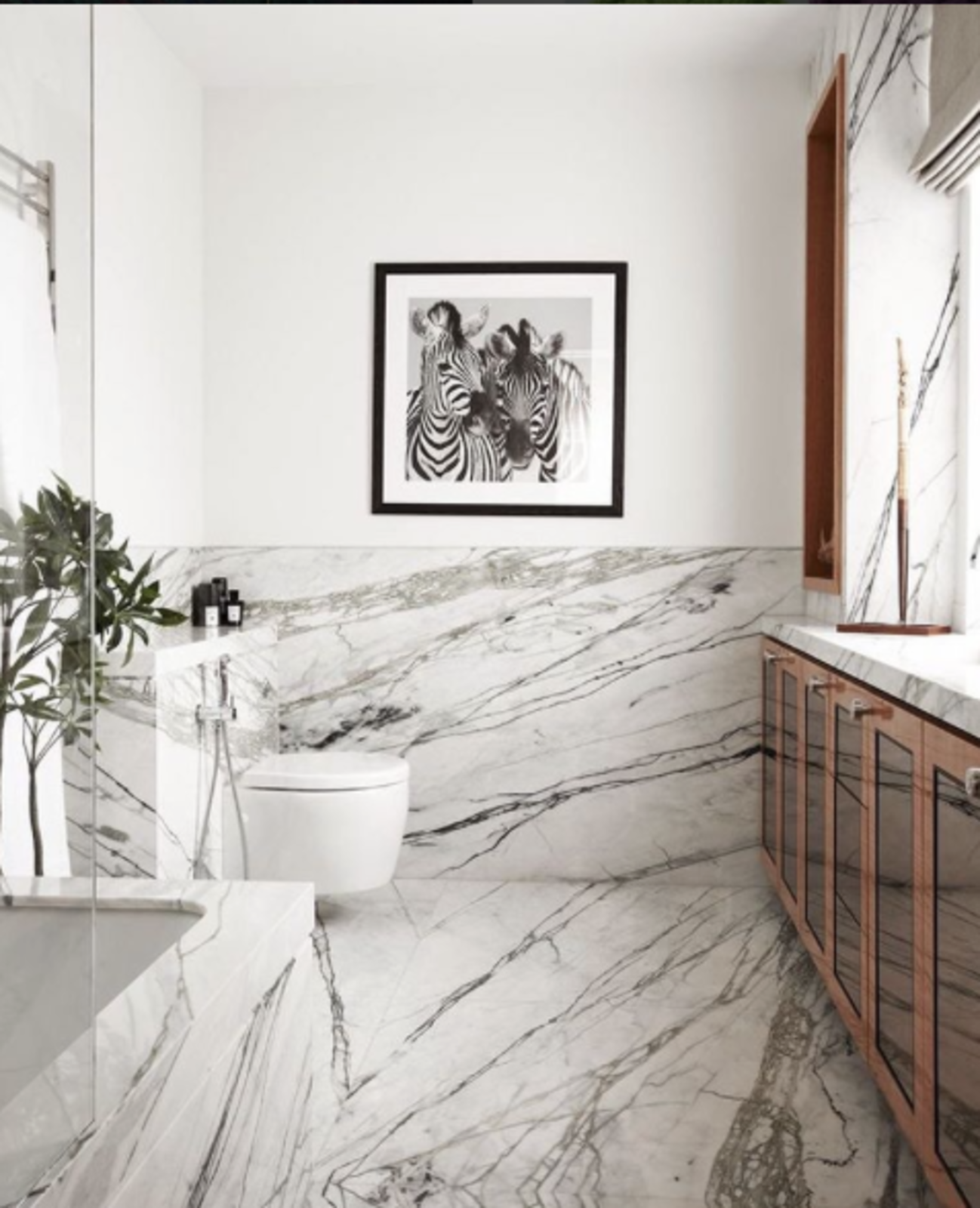 In this picture from @_decoh, the veiny marble is explicitly referenced by hung photograph.  Bathroom from Spotted on Instagram: Five Totally Different Styles for Your Bathroom