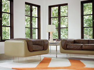 To highlight the existing architecture of the home, Hill   retained the dark polish of   the casement windows, which   she finds enhances period details instead of undermining   them. In the rear sunroom, the vintage Case Study furniture pieces with Plexiglas bases are from Metro Retro   in Houston.   A Bourgie lamp by Kartell is   atop an old marble end table by Knoll, and the Gan kilim rug pictures a branch motif echoed in the kitchen and breakfast room.