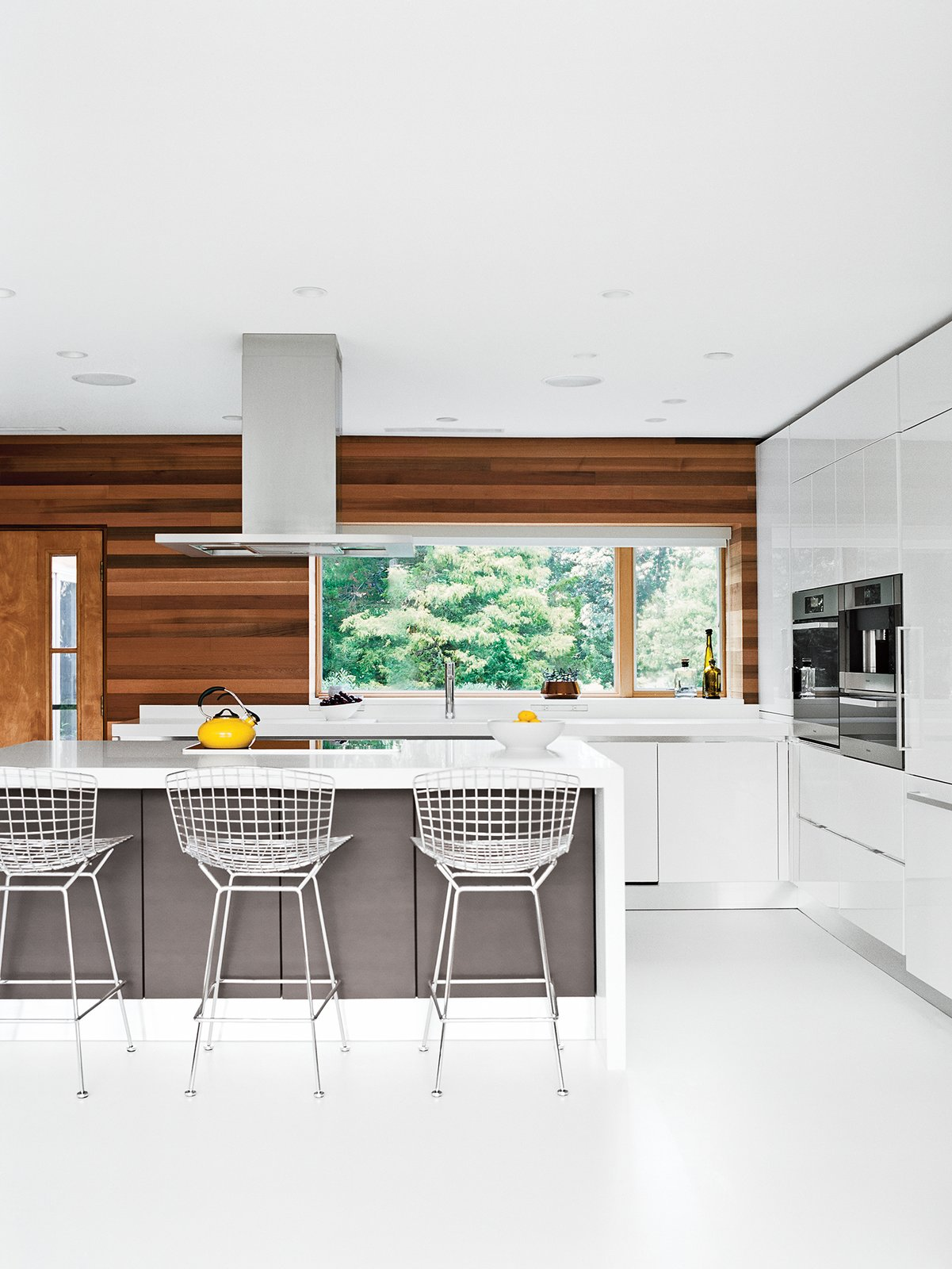 Kitchen, Wall Oven, Range Hood, White Cabinet, and Wood Cabinet Bertoia bar stools by Knoll are tucked under the island in the Scavolini Scenery kitchen. Jordan replaced the original wood flooring with white resin, a robust surface used in high-traffic environments.  Winter-White Kitchens and Bathrooms by Diana Budds from The Midcentury Spirit is Alive and Well in This Hudson Valley Escape