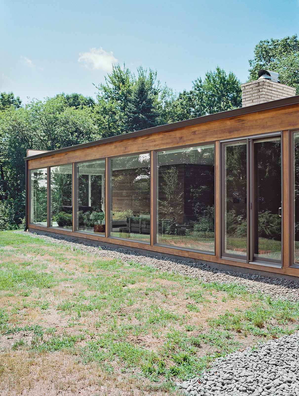 He added floor-to-ceiling windows by Andersen, which allow low winter sunlight to warm the interior in colder months. Tagged: Exterior, Mid-Century Building Type, Flat RoofLine, Wood Siding Material, and House.  Renovations from The Midcentury Spirit is Alive and Well in This Hudson Valley Escape