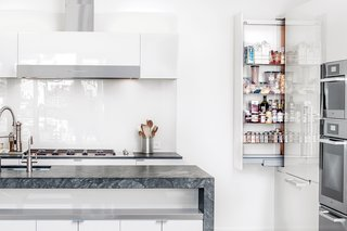 "In this sleek kitchen renovation in San Francisco, the kitchen backsplash is an easy-to-clean glass backsplash that mimics the glossy finish of the surrounding white cabinets. Painters accomplished the high-gloss finish on the cabinets of a kitchen in San Francisco by applying a coat of paint, polishing it with very high-grit sandpaper, repeating the process for each layer, then topping it with three coats of clear varnish. ""It's like an auto body,"" says builder Jeff King. ""It's incredibly beautiful."" The island provides shelving space and storage as well as a second sink, an is topped with pietra grigio marble."
