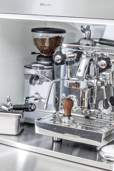 The coffee station features a professional-grade Rocket Espresso machine. Jang and King designed a stainless-steel pullout shelf for a cream and sugar station.
