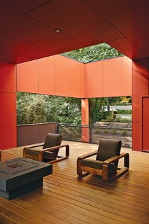 Playing off the work of artist James Turrell, as well as the front porch scheme prevalent in the South, an outside living room is half covered and half open to the leaf canopy overhead, where a pair of teak armchairs are clustered around a Laguna fire table from Restoration Hardware.