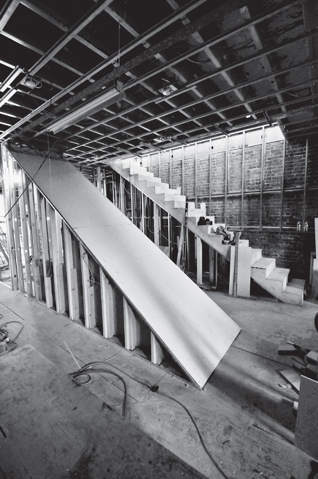 """The pair reconfigured the space inside the 2,000-square-foot duplex, creating one open area to hold a monolithic """"wedge core"""" to house the staircase, installing a new stainless-steel kitchen, and placing   a dining table designed by Gil and fabricated by Artistic Wood Crafts.  Photo 4 of 14 in A Brooklyn Couple Rehabilitate a 19th-Century Duplex"""