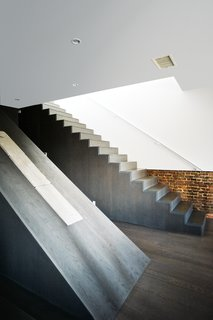 "Onwers Alex Gil and Claudia DeSimio reconfigured the space inside their 2,000-square-foot duplex, creating one open area to hold a monolithic ""wedge core"" to house the staircase. ""The older the building, the more you can adhere to older codes, which gives you more liberty,"" says Gil, who heads the architecture firm Spacecutter."