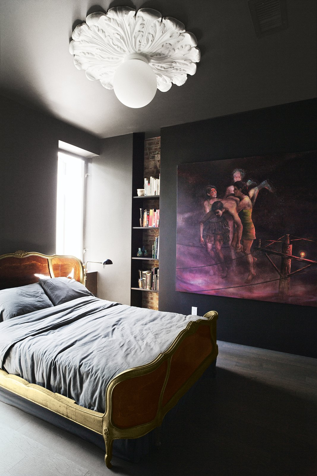 The bedroom is tucked in the back of the residence and doesn't receive a lot of natural light. The couple emphasized the coziness of the space by painting the walls in Space Black from Benjamin Moore and selecting an oversize artwork, Flotar, 2011, by Christian Curiel. The bed is a Louis XV–style reproduction, approximately from the 1950s, that Gil and DeSimio found on eBay.  Photo 3 of 14 in A Brooklyn Couple Rehabilitate a 19th-Century Duplex