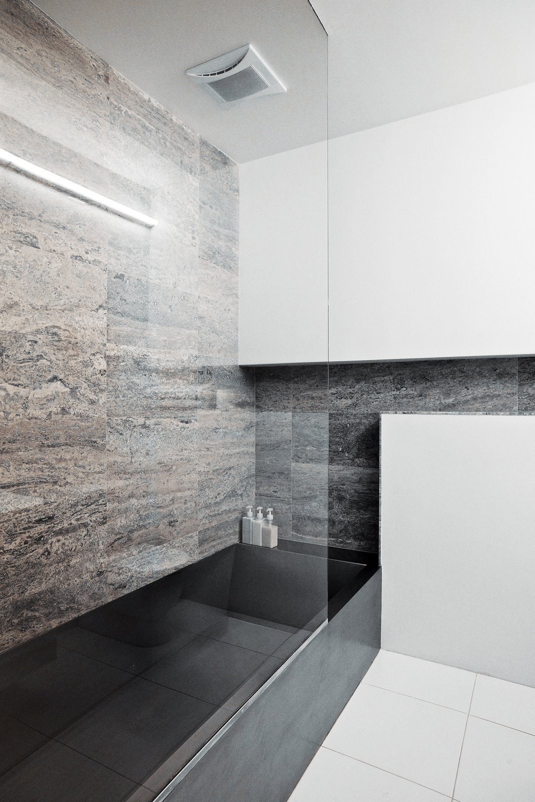 The residence's two bathrooms present distinct material identities: In the main bathroom, located on the lower level near the couple's bedroom, a custom stainless-steel bathtub designed by Gil contrasts with a wall clad in silver travertine.  Photo 11 of 14 in A Brooklyn Couple Rehabilitate a 19th-Century Duplex