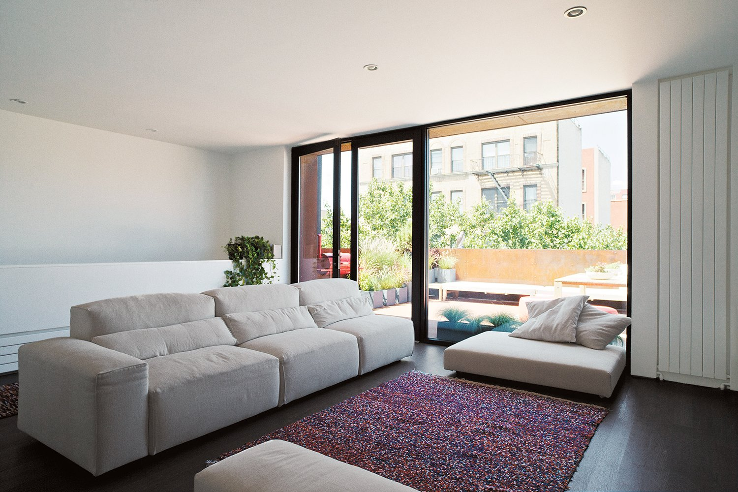 The living room-office, part of the new rooftop addition, has a Forever 715 sofa by Vibieffe and a rug the couple purchased in Morocco. The custom swing double doors feature a thermally broken aluminum frame and insulated glass.  Photo 5 of 14 in A Brooklyn Couple Rehabilitate a 19th-Century Duplex