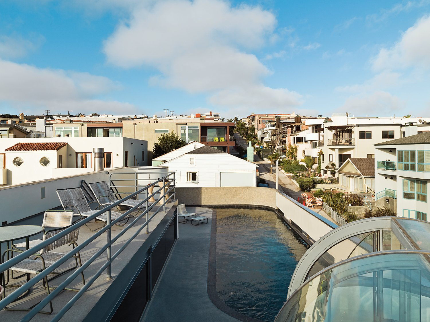 A view over the lap pool and roof deck, which provides a respite for the couple, shows the dense beachside neighborhood. The couple bought the Richard Schultz chaise longues at Studio 111 in Palm Springs.  Photo 7 of 11 in A Renovated Ray Kappe Abode in Manhattan Beach