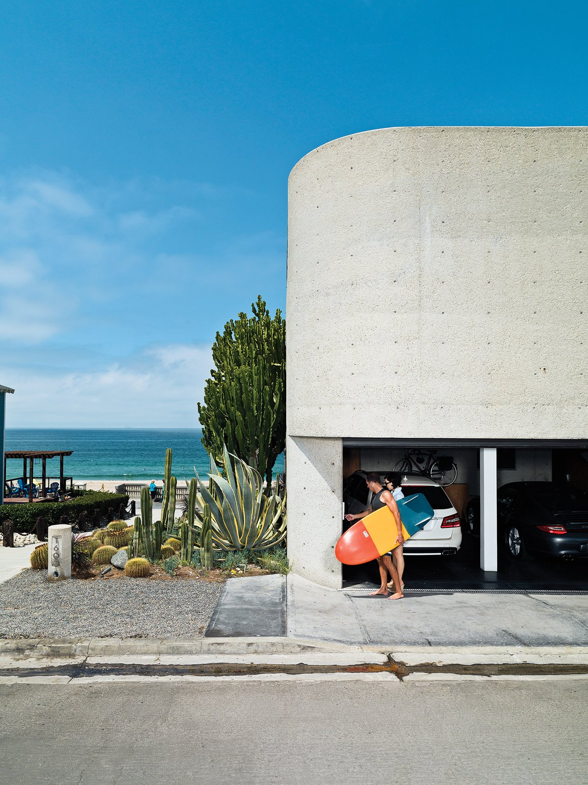 Garage and Attached Garage Room Type The streetside facade, dominated by site-poured concrete, contains the garage, from which Jacobson and Dukes escape for a quick surf.  Best Photos from A Renovated Ray Kappe Abode in Manhattan Beach