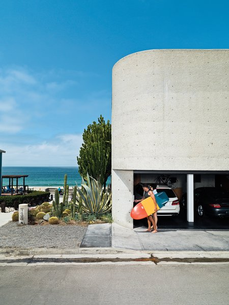 The streetside facade, dominated by site-poured concrete, contains the garage, from which Jacobson and Dukes escape for a quick surf. Tagged: Garage and Attached Garage.  Best Photos from A Renovated Ray Kappe Abode in Manhattan Beach