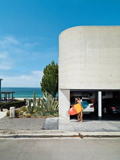 The streetside facade, dominated by site-poured concrete, contains the garage, from which Jacobson and Dukes escape for a quick surf.