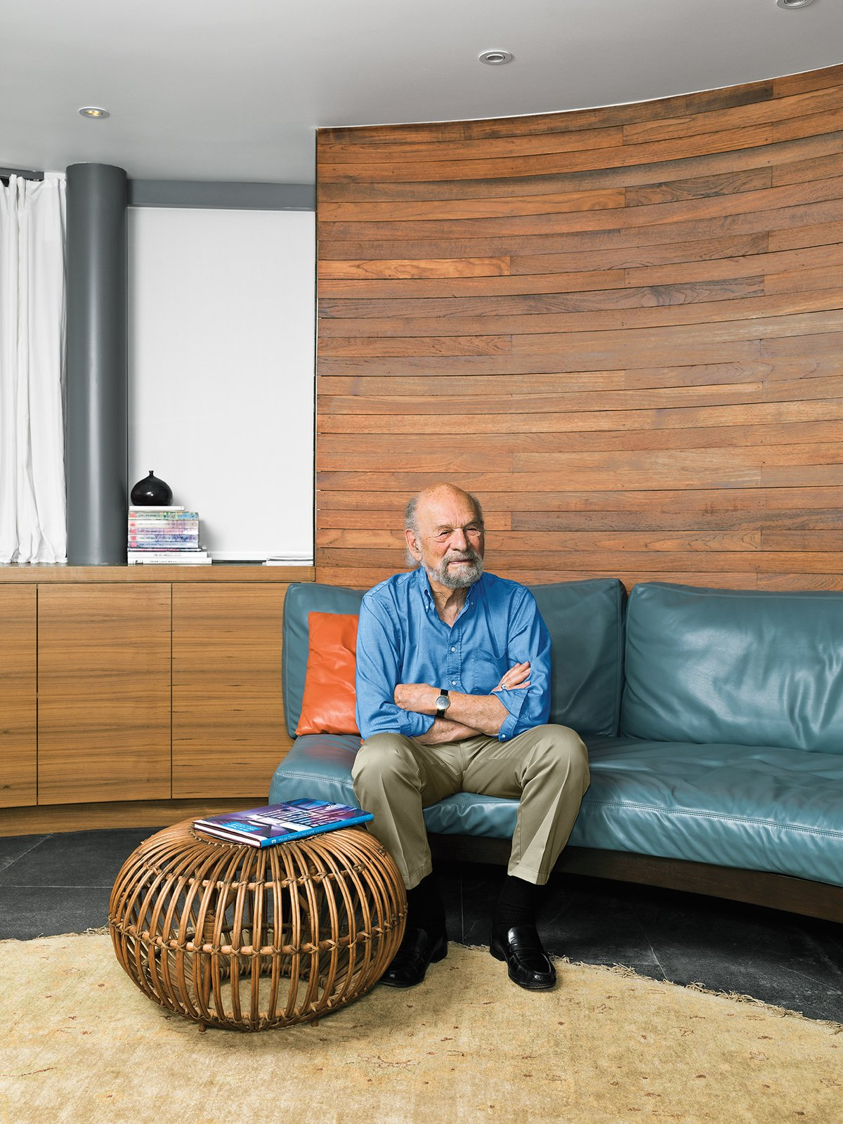 """Kappe sits on a sofa in the media room, which continues the semicircular curve. """"The form came from the [original] client's preference,"""" he notes. The rattan ottoman (found in Palm Springs) is by Franco Albini, and the carpet is from Malibu Rugs.  Photo 5 of 11 in A Renovated Ray Kappe Abode in Manhattan Beach"""