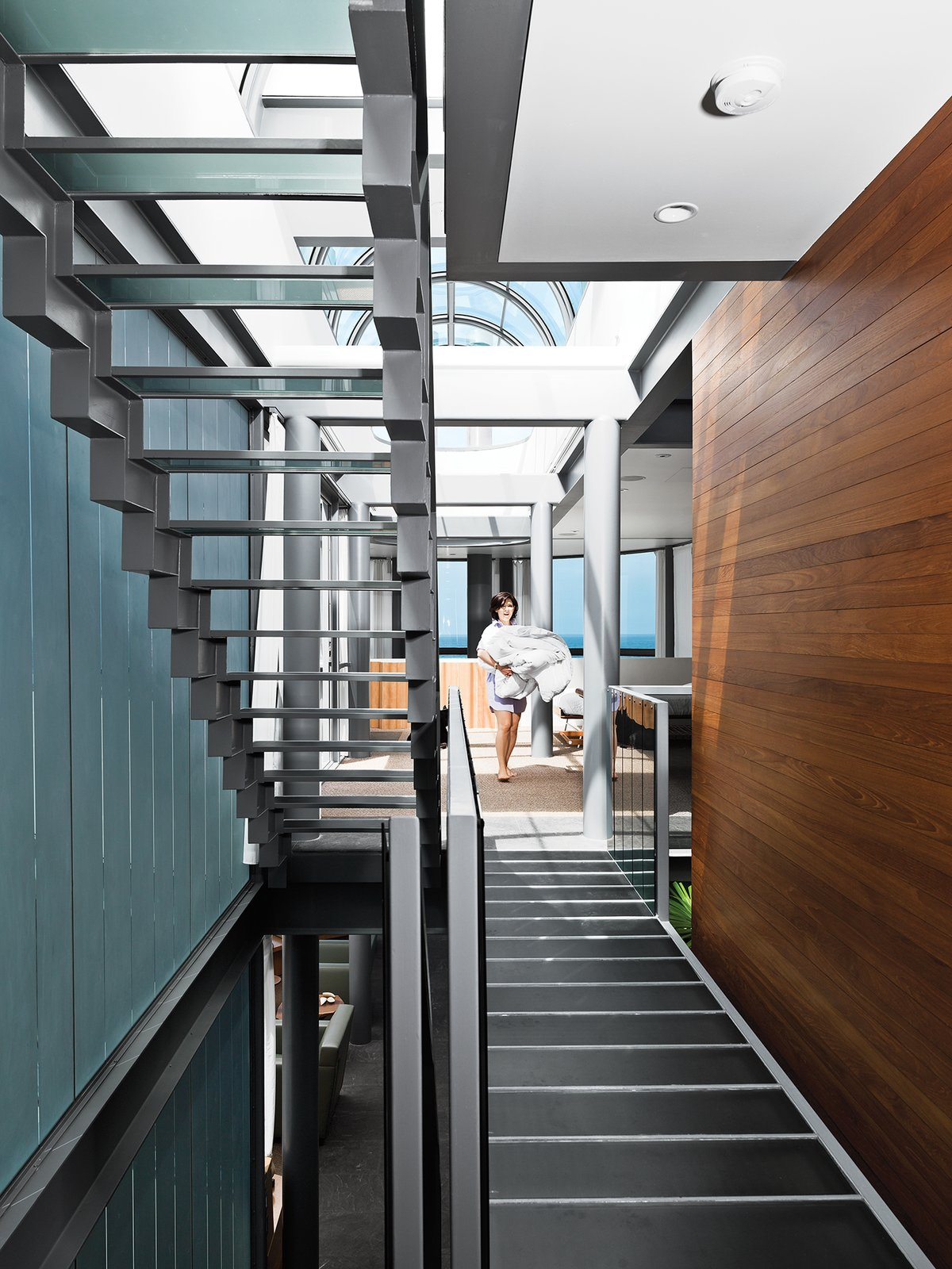 The central stairway spans the entire house from the first floor to the roof, which is crowned by a glass ceiling that allows in extra light. Areas such as the master bedroom, which is open to the living room below, fan off of the staircase, a unifying component.  Photo 9 of 11 in A Renovated Ray Kappe Abode in Manhattan Beach