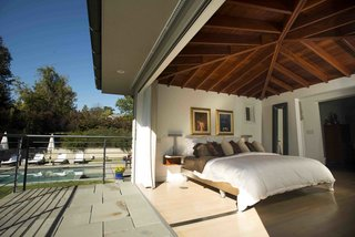 """Senhauser's clients initially wanted a retractable roof, but were persuaded to do something more practical. """"We kind of noodled around with the idea and ultimately decided that it would be easier if the bed came out on the porch than the roof rolling back over the bedroom,"""" Senhauser says. A bank of folding doors by NanaWall opens to a terrace that overlooks a swimming pool. The bed is normally stationed against a wall but can slide onto the terrace when the residents wish to sleep outside."""