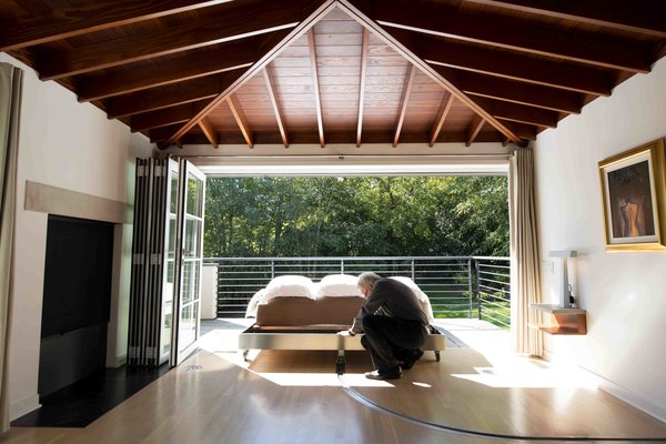 With a gentle nudge, architect John Senhauser pushes a custom bed outside onto the terrace. The bed travels along a metal track set into the white-oak floor. The ceiling rafters are Douglas fir.
