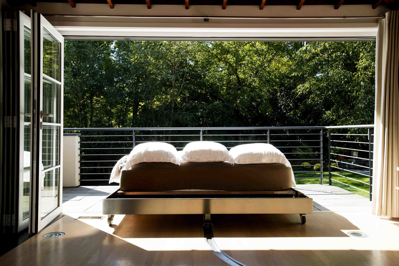"""When the bed reaches the threshold, it slides out from the frame like a drawer so it's completely outside. """"Because there are few chances to sleep outside, due to temperature or insects or humidity, the opportunities are really special,"""" Senhauser says. """"You can't do it every couple of days—it becomes a treat.""""  The Ultimate Indoor-Outdoor Bedroom  by Diana Budds"""