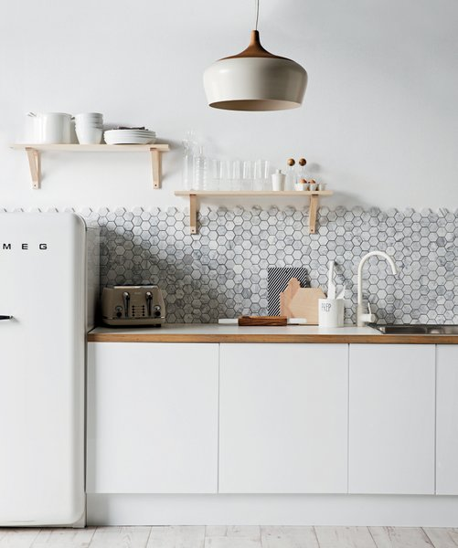 A backsplash of hexagonal Carrara marble from Australia's Di Lorenzo Tile offsets the minimalist white cabinetry and countertops in this kitchen styled by Jackie Brown.