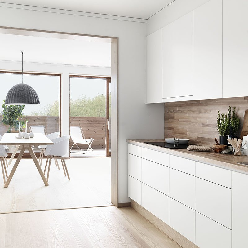 Horizontal wood planks in a light oak stain offer a natural contrast to the white cabinetry in this Swedish kitchen via folkhem.se. Photo by Petra Bindel.  Winter-White Kitchens and Bathrooms by Diana Budds