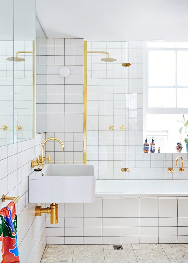 In a Melbourne home, gold fixtures and white subway tile mix in the bathroom.  Winter-White Kitchens and Bathrooms by Diana Budds