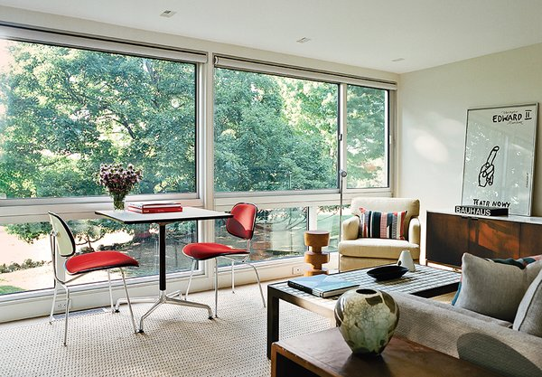 A Universal Base Table and a pair of upholstered Molded Plywood Dining Chairs, all by Charles and Ray Eames for Herman Miller, are positioned by the window.  Photo 4 of 13 in Can You Believe This House Used to be a Dilapidated Toolshed?