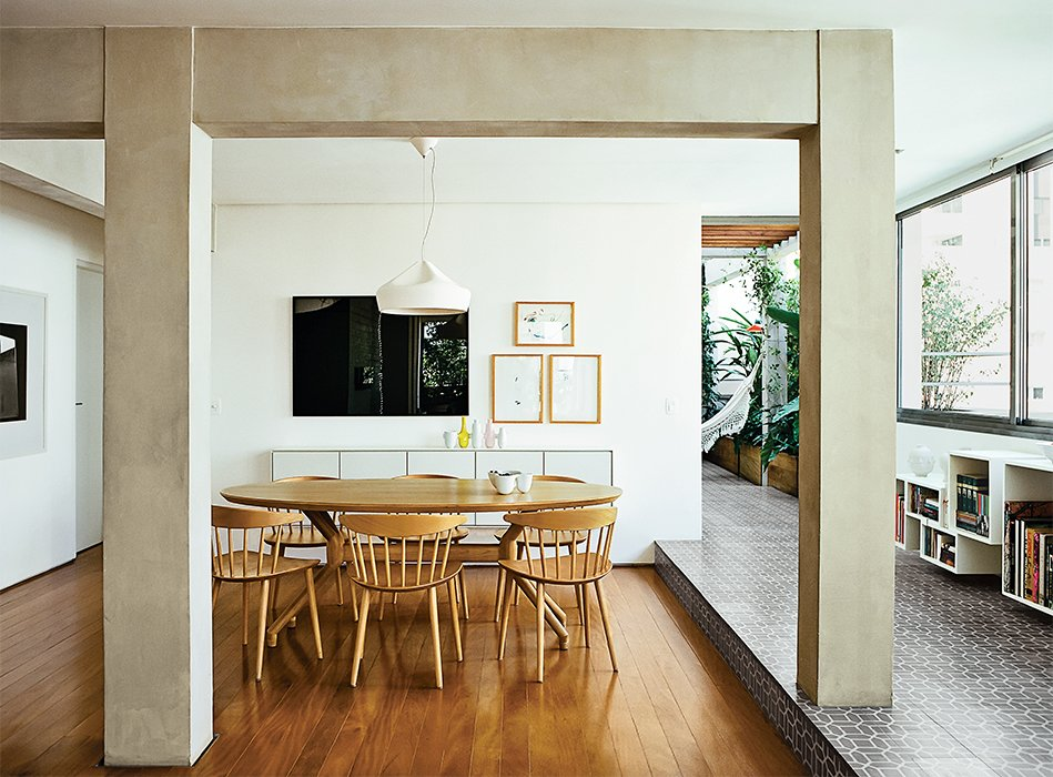 Dining Room, Table, Chair, Pendant Lighting, and Medium Hardwood Floor They replaced the tile floor with perobinha, an inexpensive local wood, and enclosed part of the terrace, integrating it into the dining room. J104 chairs by Jørgen Bækmark for Hay are arranged around a freijo wood dining table by Etel Carmona.  Photo 4 of 15 in Amazing Garden Oasis in São Paulo Born from a Five-Year Search and Renovation