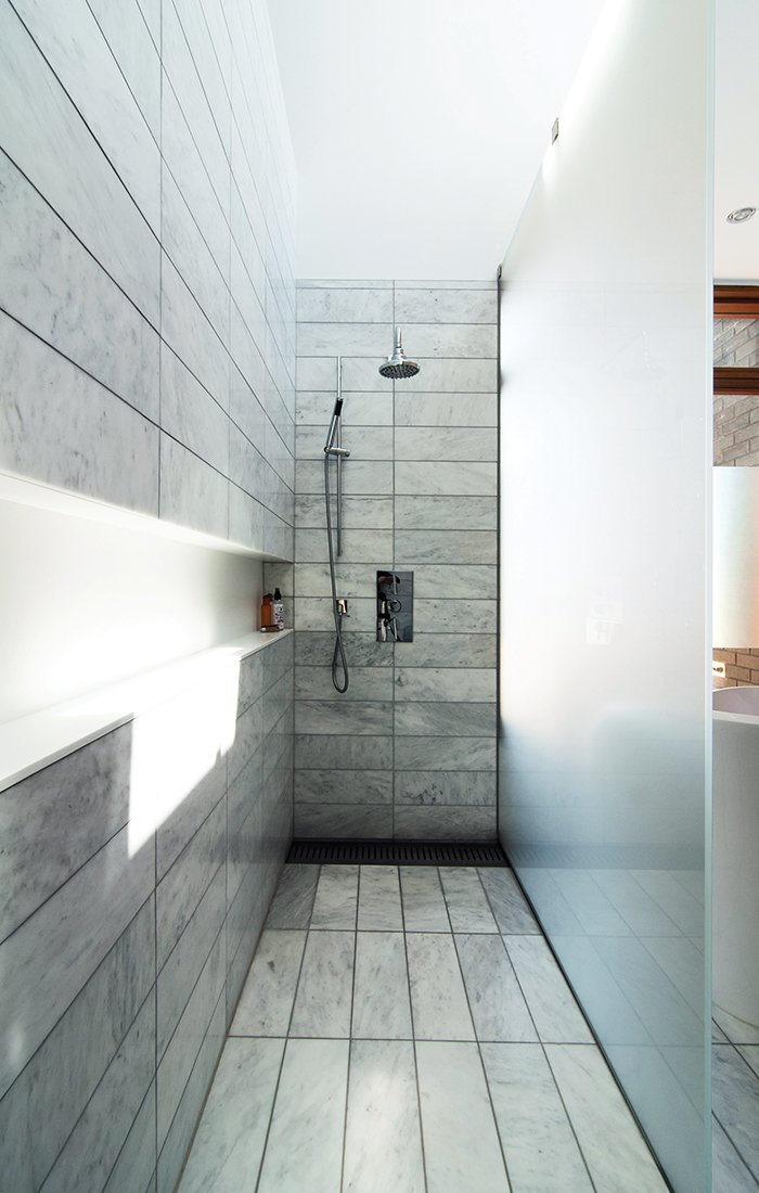 "Bath Room, Enclosed Shower, and Full Shower When this Toronto couple remodeled their Tudor home, they went for a material-rich bathroom design. The standing shower is set off by etched-glass panels supported by stainless-steel hardware. There is no threshold; instead, the tile within the shower zone slopes down very slightly to a floor trough with a custom stainless-steel grille. Along the wall, a Corian shelf—""the longest soap dish in the world,""  jokes the homeowner—runs the length of the space."