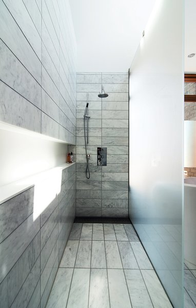 "The standing shower is set off by etched-glass panels supported by stainless-steel hardware. There is no threshold; instead, the tile within the shower zone slopes down very slightly to a floor trough with a custom stainless-steel grille. Along the wall, a Corian shelf—""the longest soap dish in the world,"" resident Don Evans jokes—runs the length of the space."