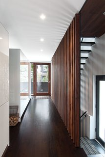 A grille of walnut slats, designed by Syme and made by the local millworkers MCM, delineates the edge of a new stair with open treads made of hot-rolled steel. Tall Bulthaup cabinets mark the edge of the dining area; Evans, a mechanical engineer, had them custom-made to conceal heating ducts that vent almost invisibly through the top edge.