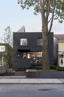 The transformed facade features dark gray stained-masonry.