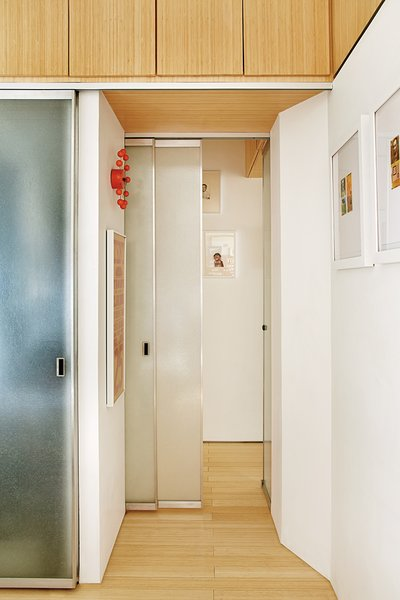 The architects designed the bamboo-plywood storage compartments above the hallway, bathroom, and bedroom closet.