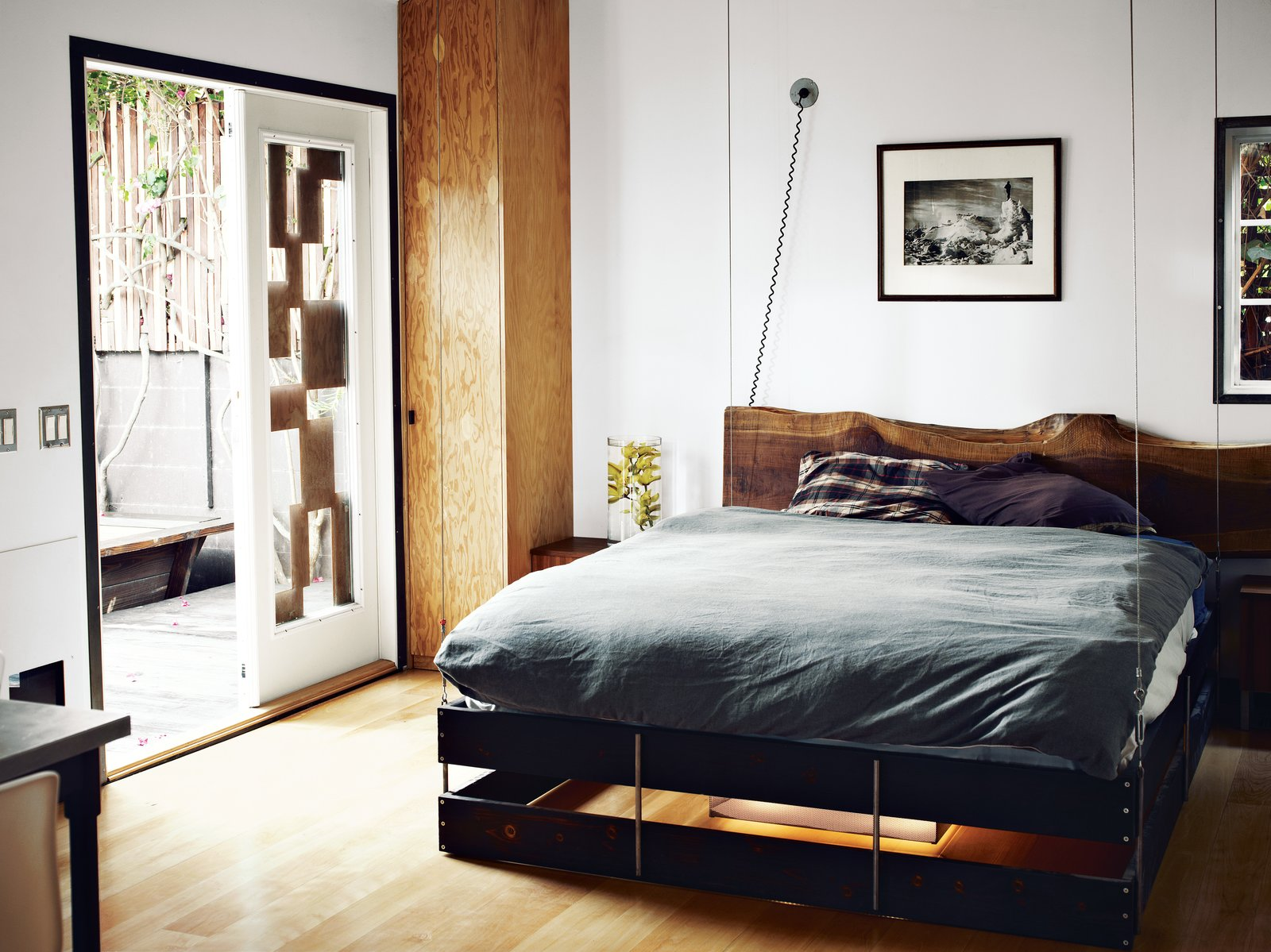 Bedroom, Bed, and Medium Hardwood Floor The bed was designed to hang from the ceiling and can be hoisted up and pulled down as needed.  Bedrooms by Dwell from The Tiny Hollywood Home of Mad Men's Vincent Kartheiser