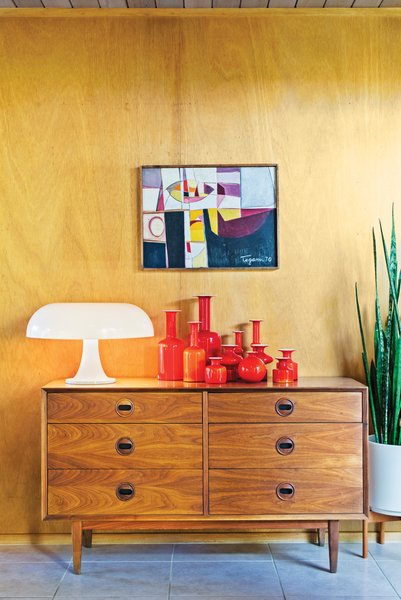 A vintage chest of drawers supports the playful forms of a Nesso lamp, designed by Giancarlo Mattioli for Artemide, and a collection of Holmegaard ceramics.