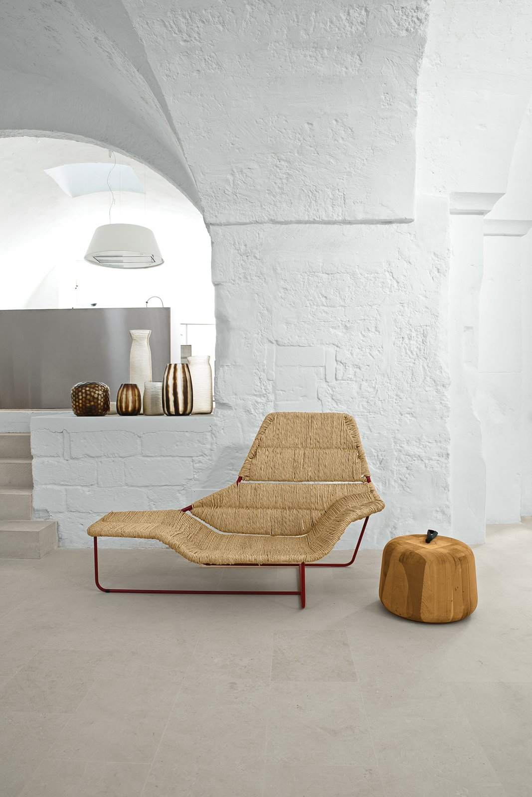 Serafini and Palomba's vacation home is a cavernous showcase for their own designs. In the living room, they created a one-off version of their Lama chaise longue, originally designed for Zanotta. The Zen Apple side table, also theirs, is from the Sen Line Collection by Exteta. The vases are by Guaxs.  Photo 2 of 8 in Modern Meets Ancient in a Renovated Italian Vacation Home