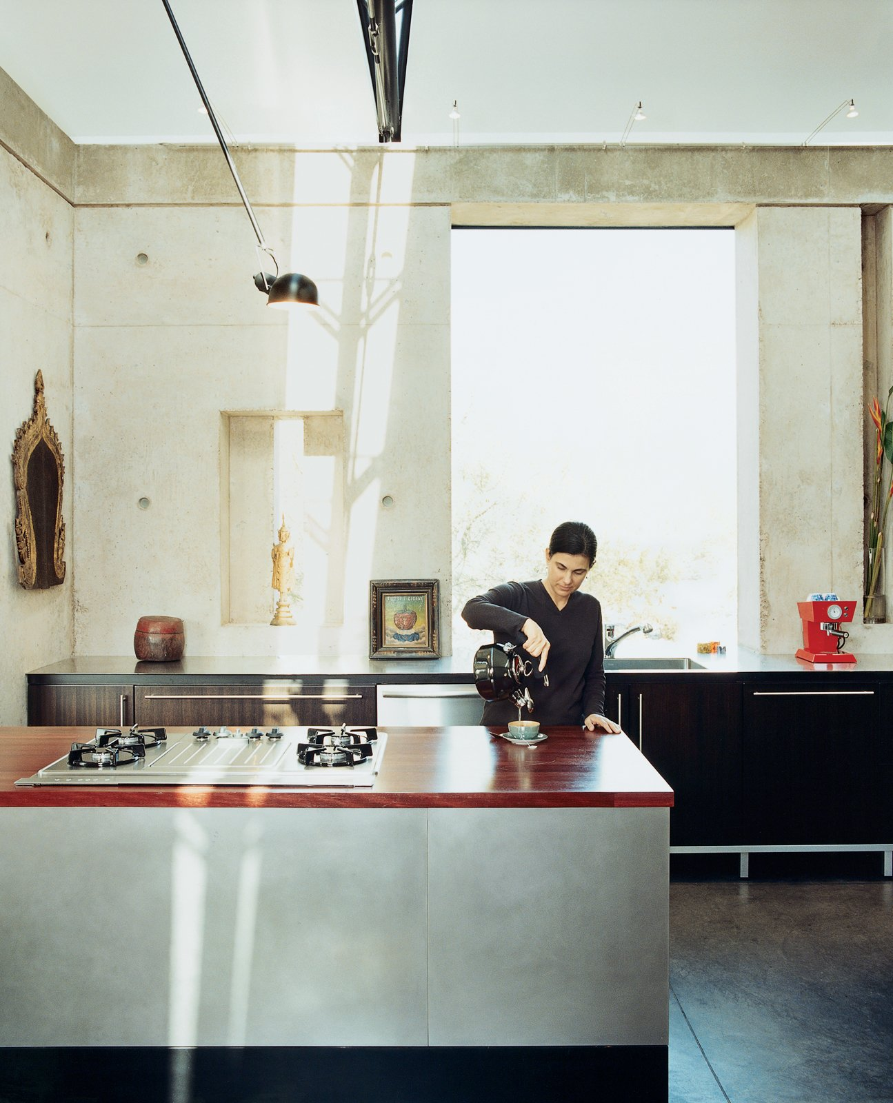 Kitchen, Wood Counter, Concrete Floor, Cooktops, Ceiling Lighting, Drop In Sink, Stone Slab Backsplashe, Dishwasher, and Accent Lighting The House of Earth + Light had been featured in the pages of the New York Times and on the cover of Dwell's premiere issue, and was revisited years later. In the kitchen, an elegant palette of materials defines the open space. The rear counter is sanded stainless steel; the island counter is Purpleheart (an exotic hardwood) with a range by Dacor.  Photos from Love's Labors Found