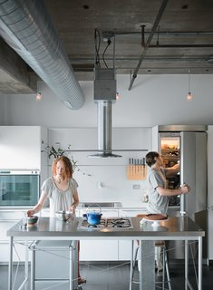 """In Chicago's Lower West Side, editorial director Chelsea Jackson and and her chef husband Arthur renovated their fourth-floor condominium to include a custom Bulthaup kitchen. """"We wanted to find a kitchen island that would be light enough to make the room seem large while still standing up to heavy-duty cooking,"""" Chelsea notes. Calls to kitchen retailers were fruitless until Arthur reached the Bulthaup showroom, where the staff suggested he come check out a floor model of the discontinued System 20 kitchen. The stainless steel island, with its precise profile and gas cooktop, was exactly what the couple was after, and they bought it on the spot. A full Bulthaup kitchen—completed with components from the B3 range—would soon become the centerpiece of their new home."""