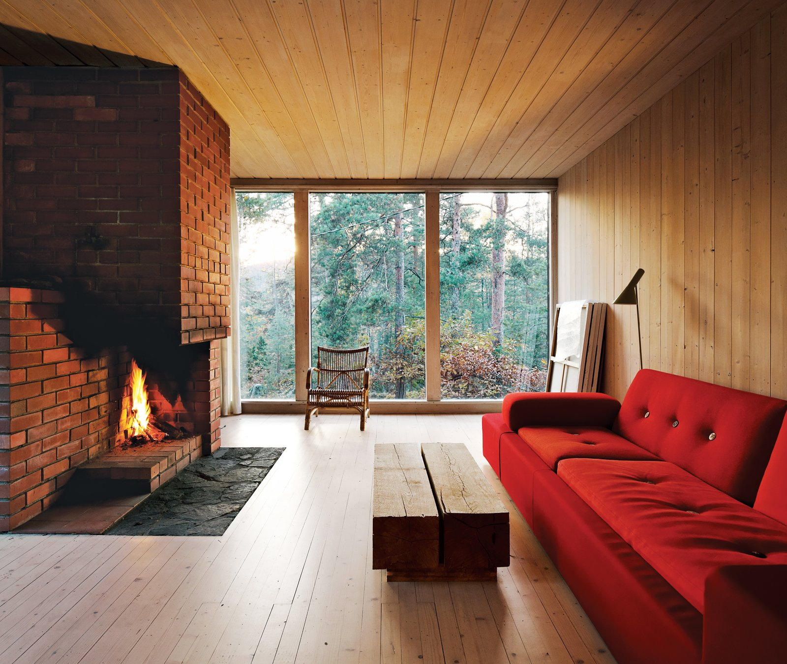 Living Room, Sofa, and Standard Layout Fireplace The interiors are clad in white-glazed pine, a contrast to the black-stained facade. The brick fireplace is original. Near a Polder sofa by Hella Jongerius for Vitra is a coffee table of Sævik's design. The rocking chair is vintage and came with the house.  430 Cabin by Diana Budds from Cozy Scandinavian Abodes