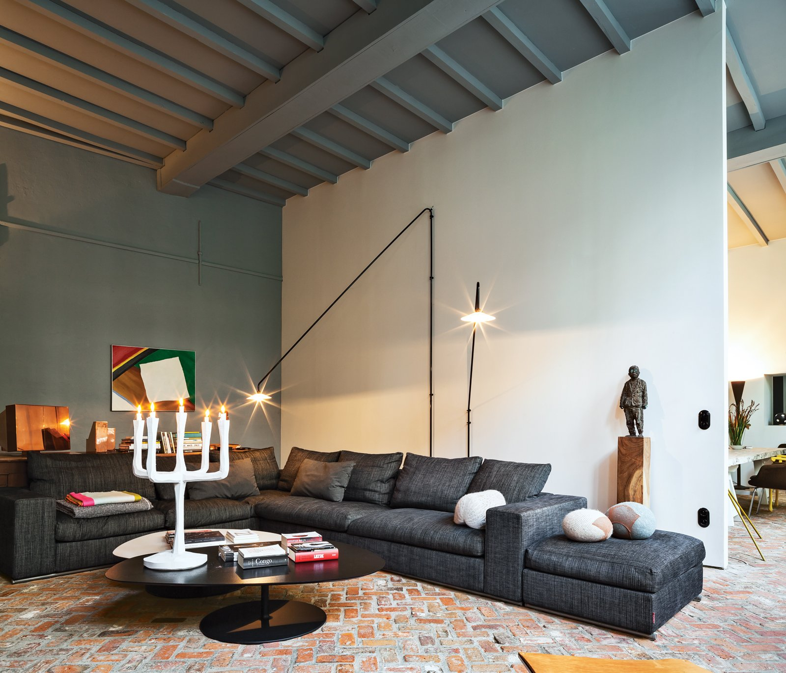 Living Room, Brick Floor, Sofa, Sectional, Floor Lighting, and Table Lighting The room also contains a sofa by Flexform, cushions from textile firm Chevalier Masson, a Jens Fager candelabra, and a painting by Roger Raveel.  Photos from An Eclectic Living Room in Antwerp