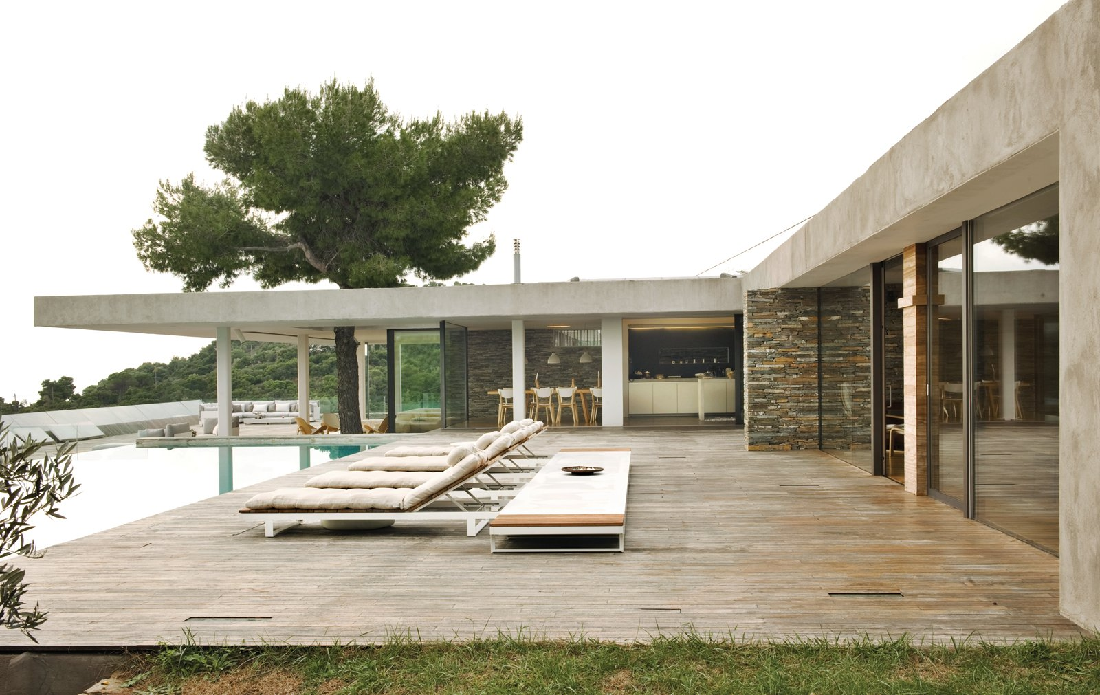 Stone walls, a pine tree exploding out of a deep overhang, iroko decking, outdoor rooms, a glassy swimming pool, and endless views of the sea make this home a paragon of indoor-outdoor living.  Photo 1 of 13 in An Idyllic Vacation Home in Greece