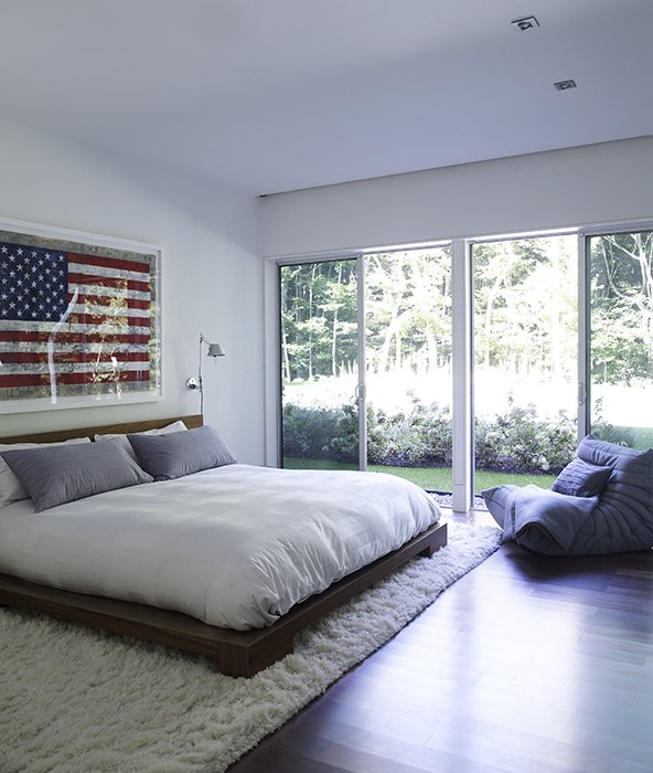 Bedroom, Bed, and Rug Floor The glass-walled master suite opens to the surrounding forest and gardens and feels totally separate from the children's and guest bedrooms upstairs.  Photo 7 of 12 in Art-Filled Hamptons Vacation Home