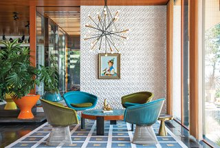 """""""There's no right answer except to play and experiment,"""" Adler says about furnishing the interior. He reupholstered vintage Warren Platner chairs with velvet from Kravet. Drawings by Eva Hesse inspired the custom ceramic wall tile. Adler also created the coffee table, rug, planters, and gold stool. The pendant lamp is from Rewire in Los Angeles and the artwork is by Jean-Pierre Clément."""