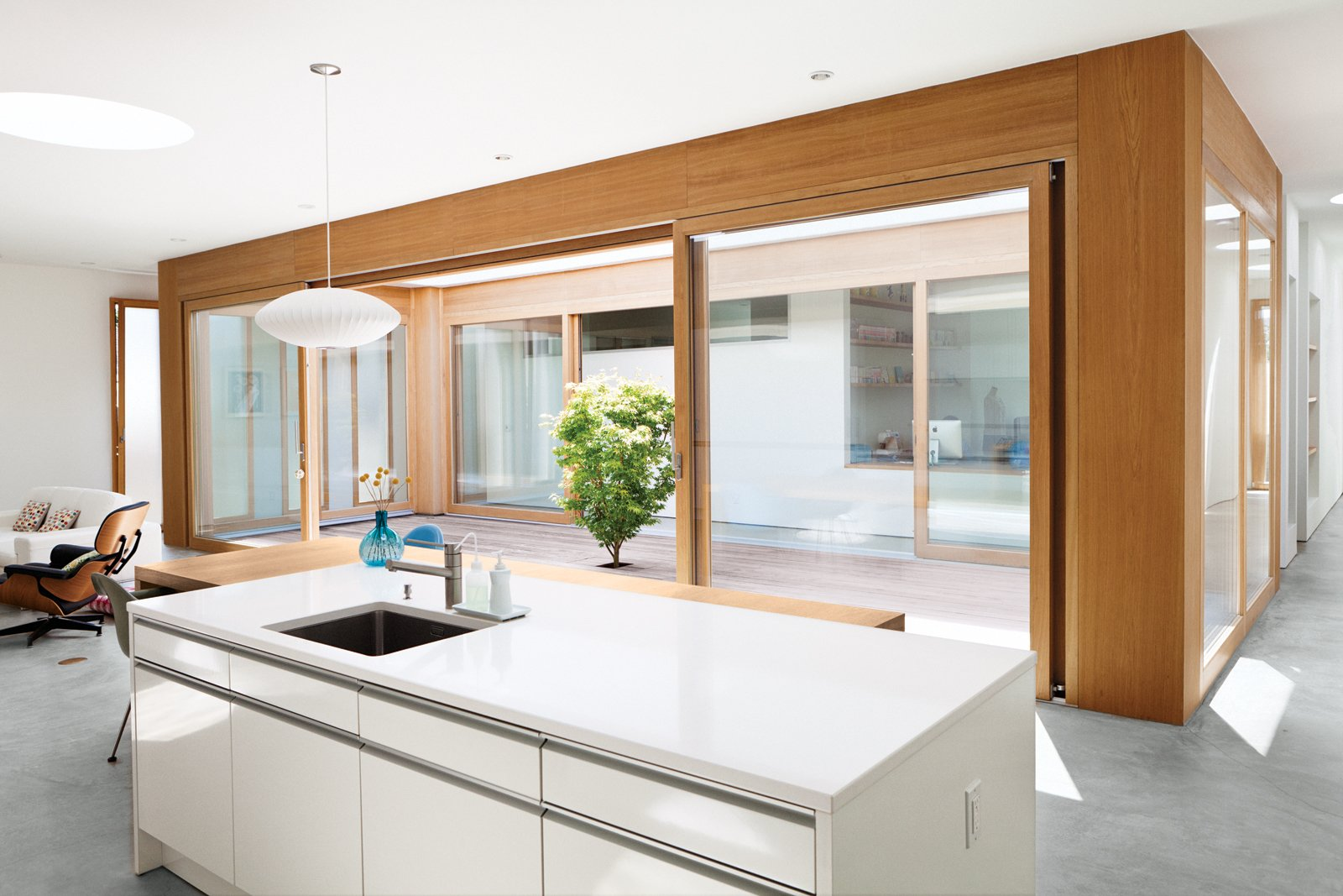 Kitchen, White Cabinet, Concrete Floor, Pendant Lighting, and Undermount Sink For Paul and Shoko Shozi, a pair of retiring Angelenos, the goal was to shut out the neighborhood but bring in the sunny skies. Their new prefab home, the Tatami House, designed by Swiss architect Roger Kurath of Design*21, makes a central courtyard the physical, and maybe even the spiritual, center of the home. Because the Japanese maple in the courtyard had to be planted before the ipe deck was laid, Kurath designed a small removable panel to allow access to the tree's base. The Shozis can pull up the bit of decking to tend to the tree and replace it when they're through. And because the boards line up perfectly, only the gardener need know it's there. From the kitchen and living room you're well connected to the courtyard and the rest of the house.   Photo 1 of 19 in Looking Inward