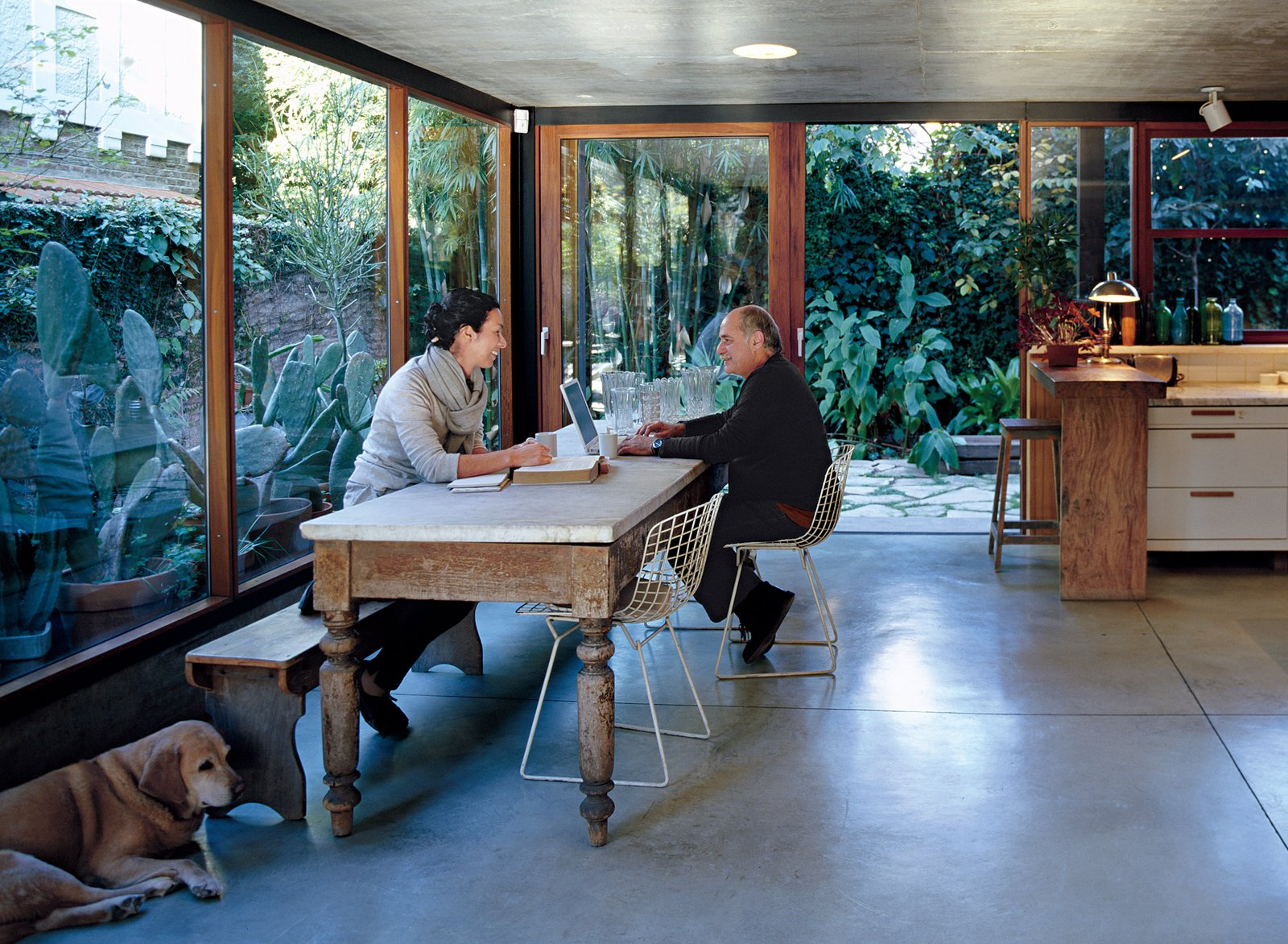 Dining Room, Chair, Table, Concrete Floor, Table Lighting, Bench, Stools, Recessed Lighting, and Ceiling Lighting The couple relax in their open-plan kitchen with their twelve-year-old lab, Uma.  Best Photos from Net Assets
